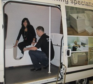 Customer testing a walk in bath in Absolute Mobility Mobile Showroom
