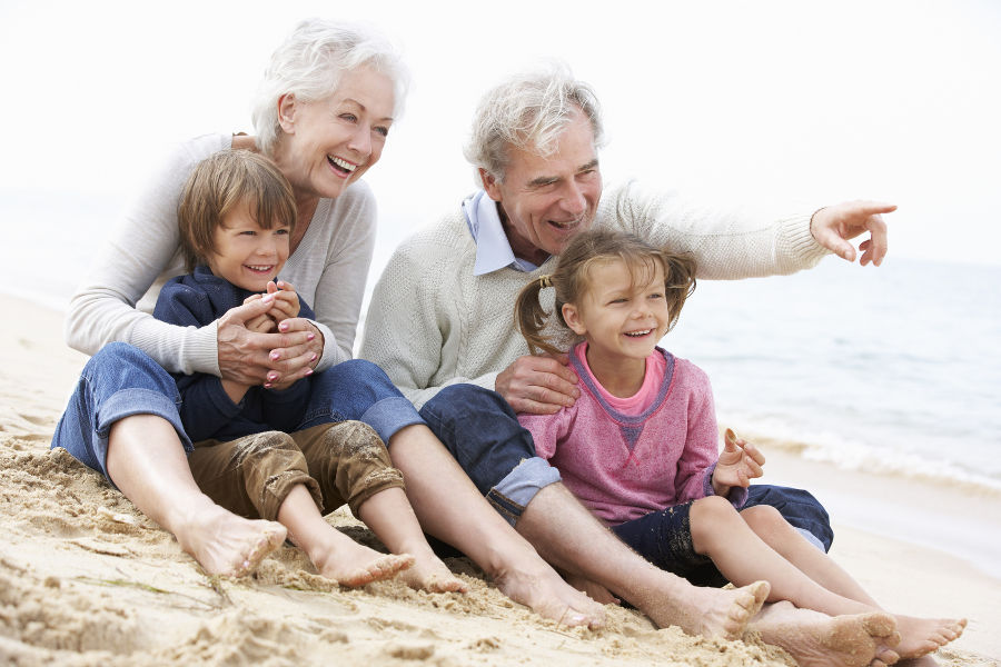 grandparents and children sitting on beach