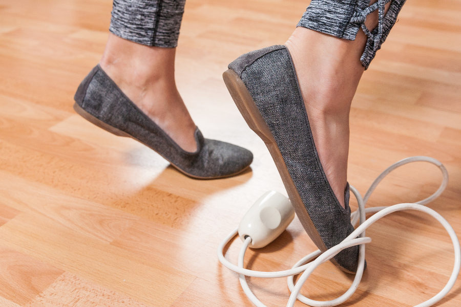 womens feet tripping over electrical cord